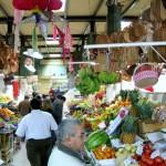 Fresh fruit stalls and a hanging piñata