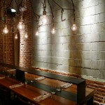 A communal table surrounded by exposed brick and hanging Edison lightbulbs at Bestia restaurant in downtown LA