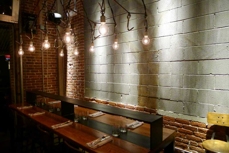 A Communal Table Surrounded By Exposed Brick And Hanging Edison - Community table restaurant